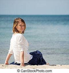 Una mujer sentada en la playa
