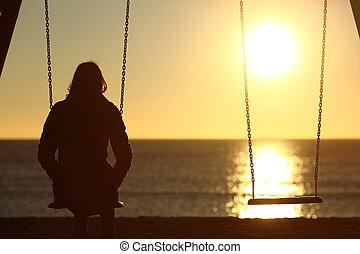 Una mujer solitaria mirando el atardecer sola en invierno