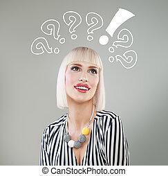 Una mujer sonriente con interrogantes sobre la cabeza mirando hacia arriba