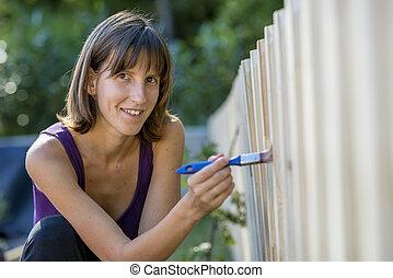 Una mujer sonriente pintando una valla de jardín