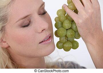 Una mujer sosteniendo un montón de uvas junto a su cara