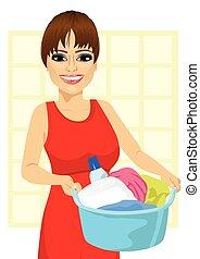 Una mujer sosteniendo una canasta de ropa sucia