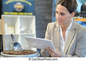 Una mujer sosteniendo una tableta junto al contenedor de granos de café