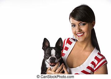 Una mujer sujetando a un perro terrier.
