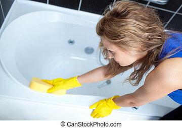Una mujer trabajadora que limpia un baño