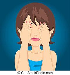 Una mujer triste cubriendo los ojos