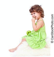 Una niña adorable comiendo manzana verde