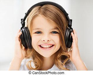 Una niña con auriculares en casa