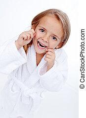 Una niña con hilo dental