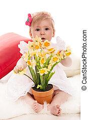 Una niña con narcisos en una olla