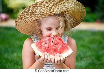 Una niña con sombrero de paja con una gran rebanada de sandía sentada en césped verde en el parque de verano.