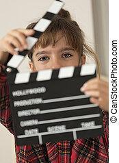 Una niña de 10 años con una tabla de cien en sus manos.