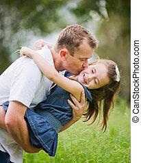 Una niña de 6 años disfrutando un momento de diversión con su padre que la está besando en la mejilla