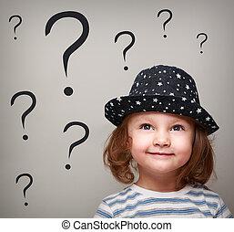 Una niña feliz con sombrero mirando muchas preguntas sobre la cabeza