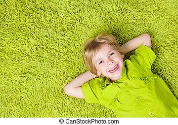 Una niña feliz en el fondo de la alfombra verde. Niño sonriendo y mirando cámara