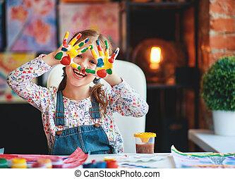 Una niña graciosa dibuja risas muestra manos sucias de pintura