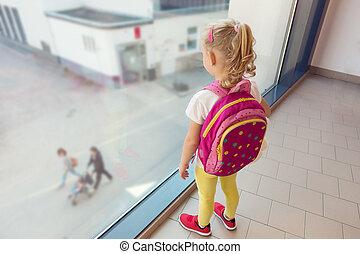 Una niña mirando por la ventana