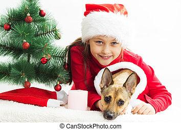 Una niña muy linda con un perro vestido con disfraces de Navidad