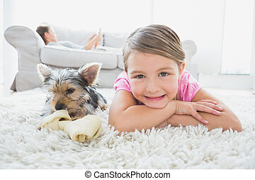 Una niña recostada en la alfombra con Terrier de Yorkshire sonriendo a la cámara en la sala de estar