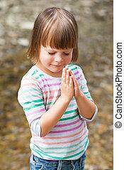 Una niña rezando