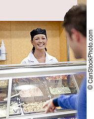 Una panadera alegre escuchando a una estudiante en la cola de la cafetería del campus