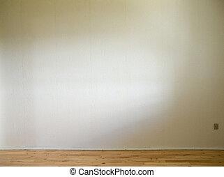 Una pared blanca con piso de madera y luz del día a un lado