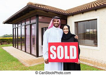 Una pareja árabe con una firma de bienes raíces vendidas