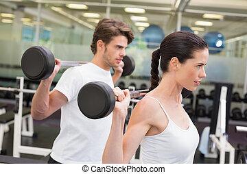 Una pareja adecuada levantando pesas juntos