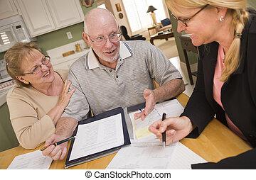 Una pareja adulta que revisa los papeles en su casa con el agente