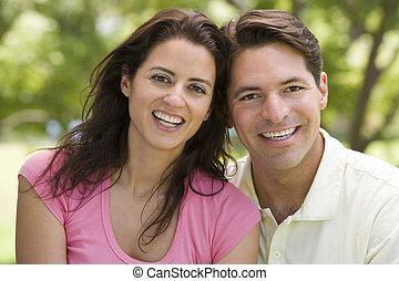 Una pareja al aire libre sonriendo
