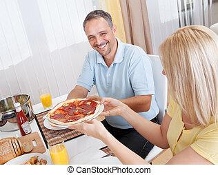 Una pareja alegre comiendo
