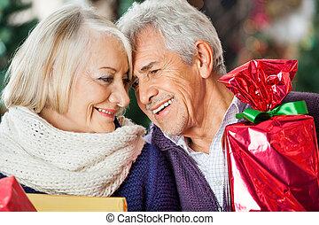 Una pareja amorosa con regalos de Navidad en la tienda