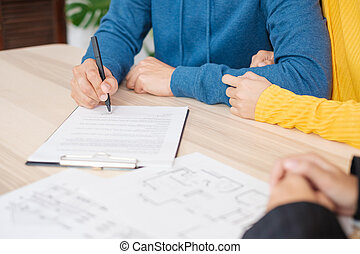 Una pareja asiática firma contrato de casa con un agente inmobiliario en casa. Comprando nuevos bienes raíces.