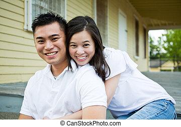 Una pareja asiática frente a su casa