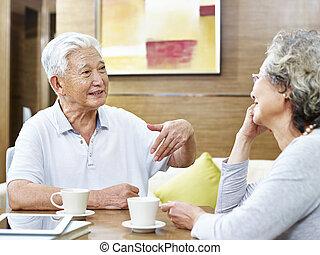 Una pareja asiática mayor teniendo una conversación en casa