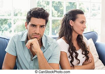 Una pareja atractiva no habla en el sofá
