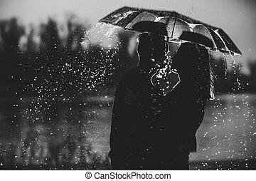 Una pareja bajo un paraguas bajo la lluvia