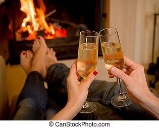 Una pareja bebiendo champán delante de un fuego