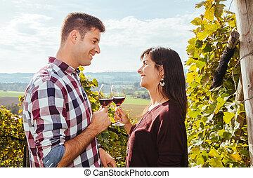 Una pareja bebiendo vino en un viñedo