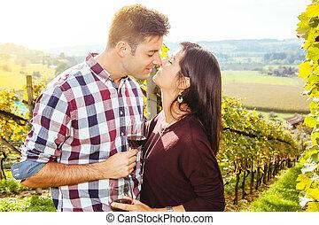 Una pareja bebiendo y besándose en un viñedo