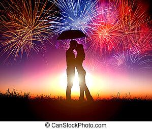 Una pareja besándose bajo un paraguas con fuegos artificiales en el cielo