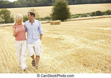 Una pareja caminando juntos por el campo cosechado de verano