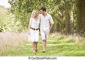 Una pareja caminando por el camino sonriendo