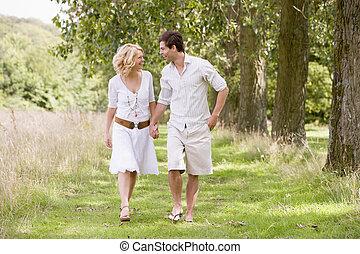Una pareja caminando por el camino sosteniendo las manos sonriendo