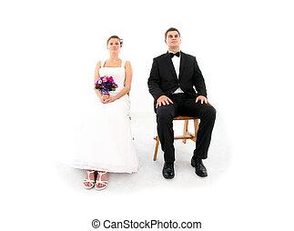 Una pareja casada sentada sobre un fondo blanco