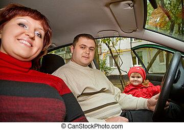 Una pareja casada y una niña se sientan en un auto cerca de un edificio
