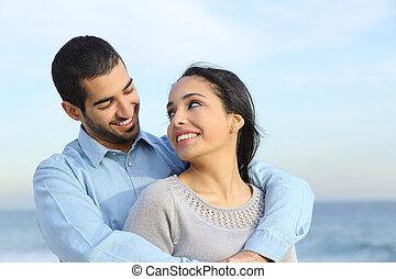 Una pareja casual árabe abrazada feliz de amor en la playa