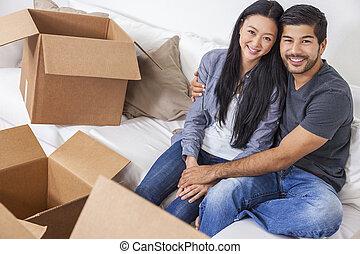 Una pareja china asiática desempacando cajas de mudanza