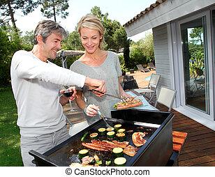 Una pareja cocinando carne en barbacoa