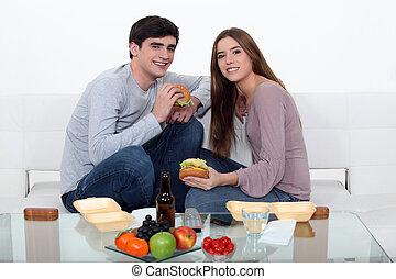 Una pareja comiendo comida rápida en el sofá